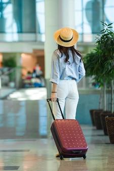 Jonge vrouw in hoed met bagage in internationale luchthaven die met haar bagage loopt.