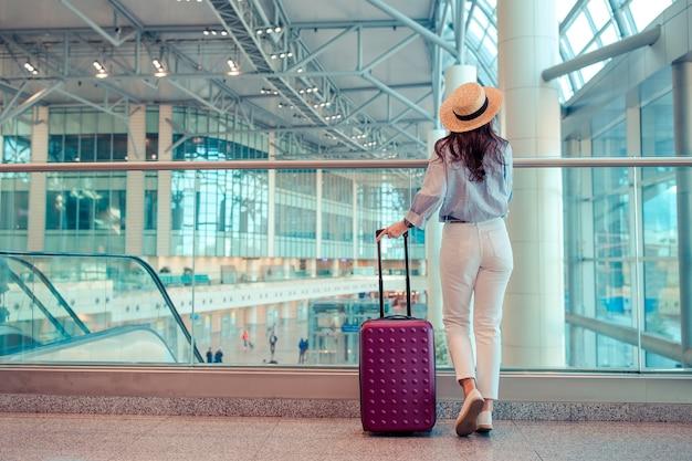 Jonge vrouw in hoed met bagage in internationale luchthaven.