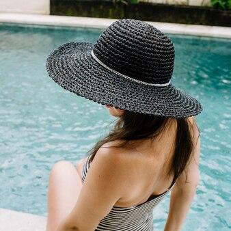 Jonge vrouw in hoed ontspannen in de buurt van zwembad