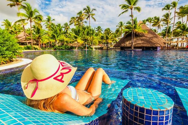 Jonge vrouw in hoed ontspannen in het zwembad