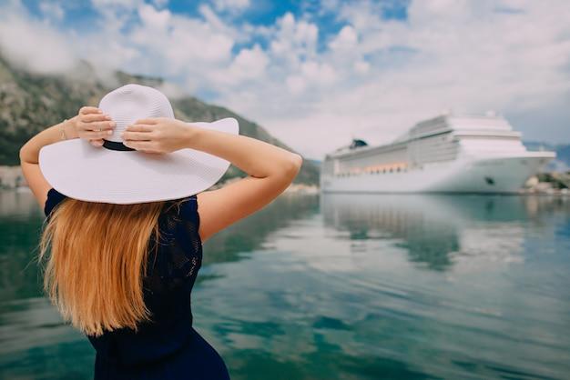 Jonge vrouw in hoed staat op cruise liner achtergrond, achteraanzicht