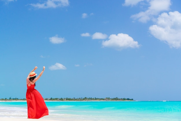 Jonge vrouw in hoed tijdens tropische strandvakantie. achteraanzicht van gelukkig meisje geniet van haar vakantie