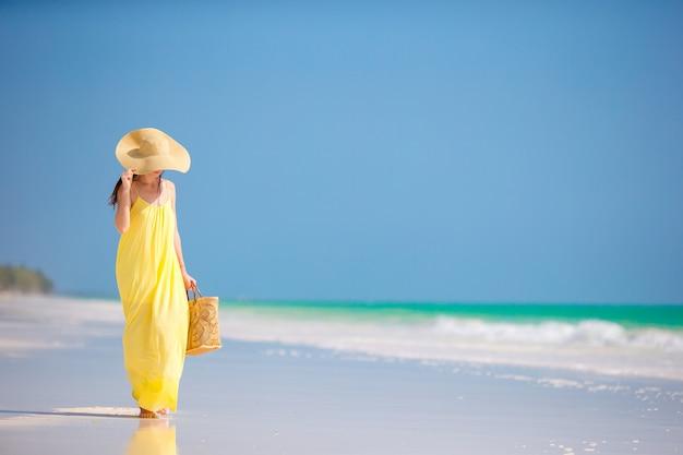 Jonge vrouw in hoed tijdens tropische strandvakantie