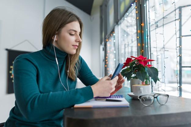 Jonge vrouw in hoofdtelefoons die smartphone voor het werk en studie gebruiken