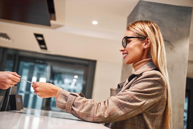 Jonge vrouw in hotel inchecken bij receptie of frontoffice krijgt sleutelkaart
