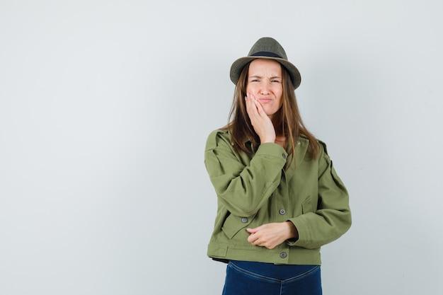 Jonge vrouw in jas, broek, hoed die aan kiespijn lijdt en ongemakkelijk, vooraanzicht kijkt.