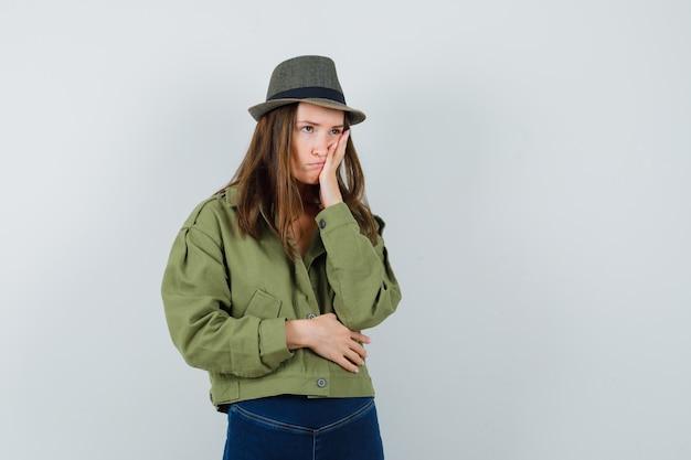 Jonge vrouw in jas, broek, hoed met hand op de wang en op zoek boos, vooraanzicht.