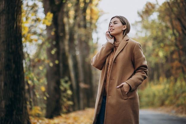Jonge vrouw in jas die zich op de weg in een de herfstpark bevindt
