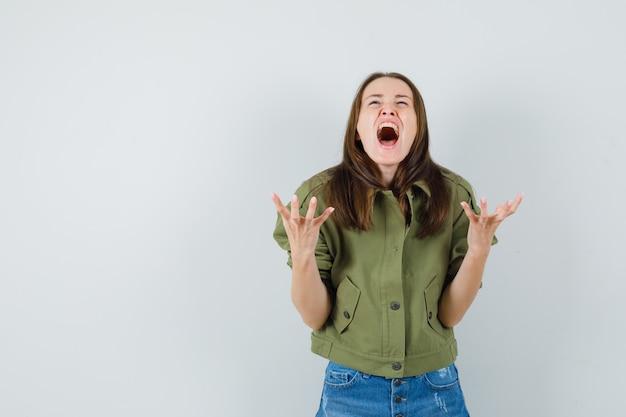 Jonge vrouw in jasje, korte broek handen op agressieve manier verhogen terwijl schreeuwen, vooraanzicht.