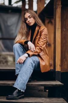 Jonge vrouw in jasje zittend op trappen
