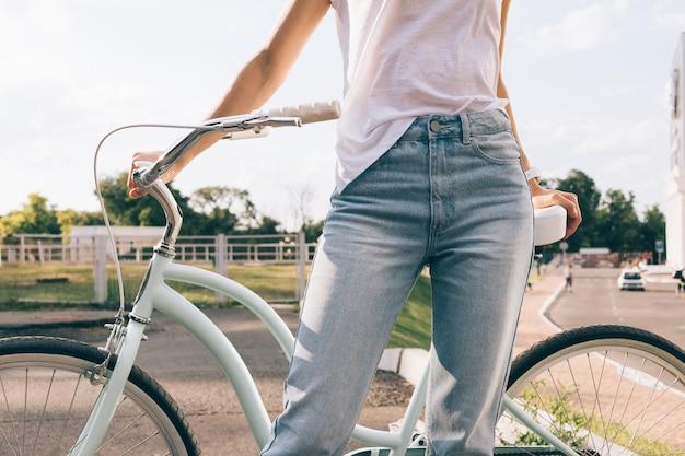 Jonge vrouw in jeans en t-shirt met een fiets in het park in de zomer