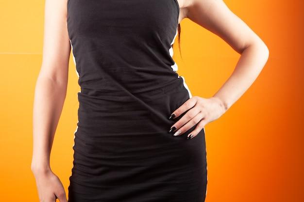 Jonge vrouw in jurk die zich voordeed op oranje achtergrond