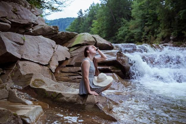 Jonge vrouw in jurk en met strooien hoed op knie zit op steen kijkend naar splashing waterfall. vreedzame kaukasische reiziger zit bij beautiful stream.