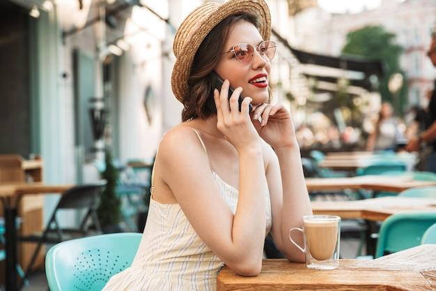 Jonge vrouw in jurk en strooien hoed praten door smartphone