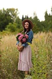 Jonge vrouw in jurk, hoed en spijkerjasje met boeket van roze bloemen hortensia,