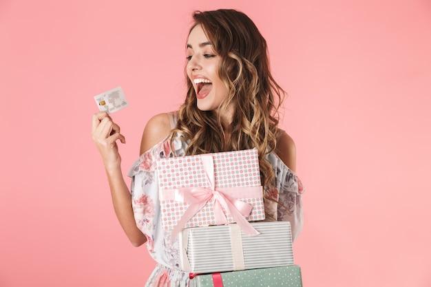 Jonge vrouw in jurk met creditcard en dozen met aankoop, geïsoleerd op roze