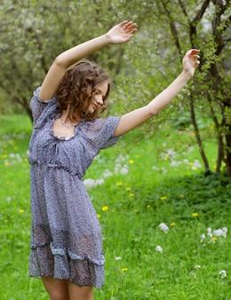 Jonge vrouw in jurk ontspannen in de tuin