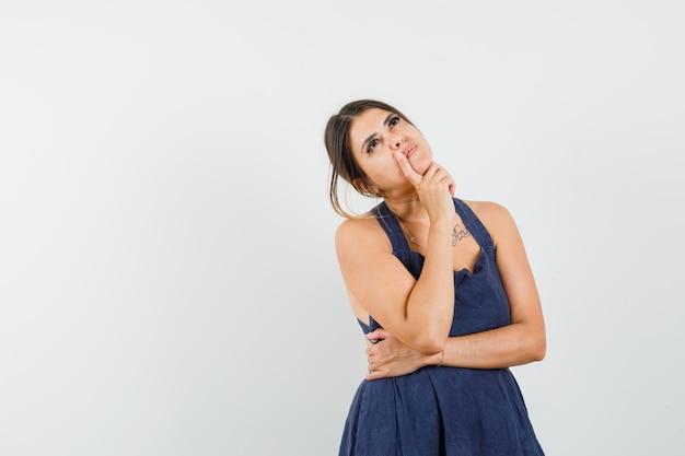 Jonge vrouw in jurk opzoeken en peinzend kijken.