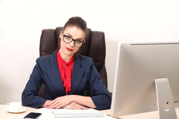Jonge vrouw in kantoor werken op bureaublad