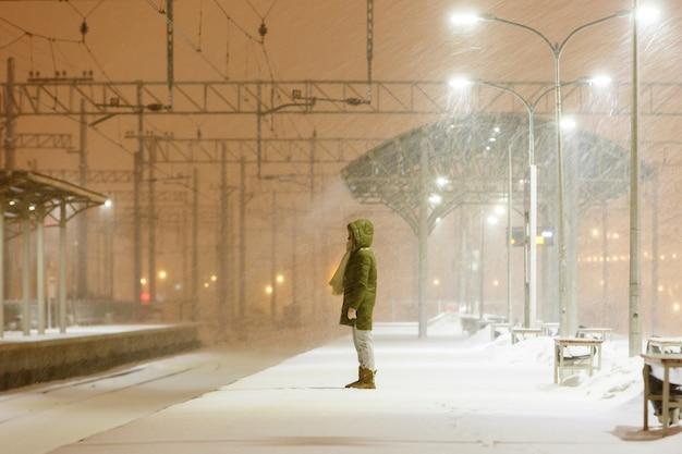 Jonge vrouw in kap op leeg perron in sneeuwstorm te wachten op een trein.