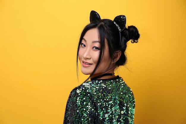 Jonge vrouw in kattenoren op gekleurde achtergrond