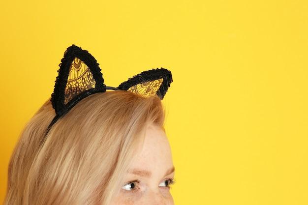 Jonge vrouw in kattenoren op kleur achtergrond, close-up