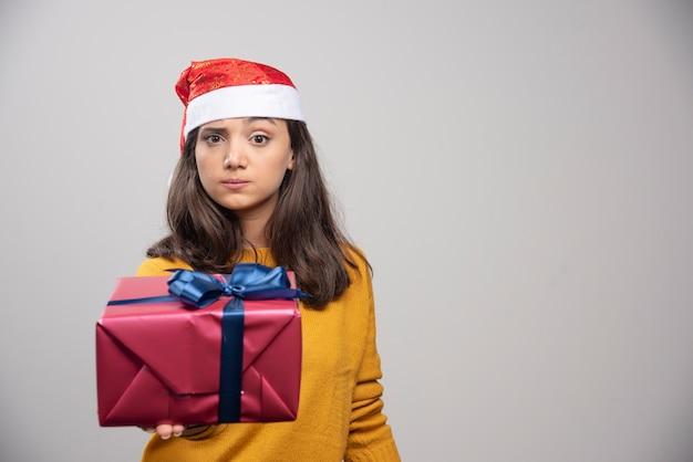 Jonge vrouw in kerstmanhoed die een giftdoos toont.