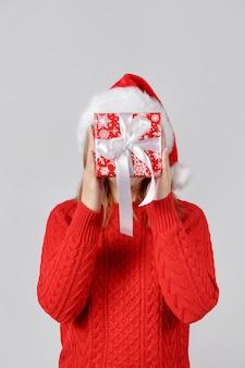 Jonge vrouw in kerstmuts bedrijf aanwezig