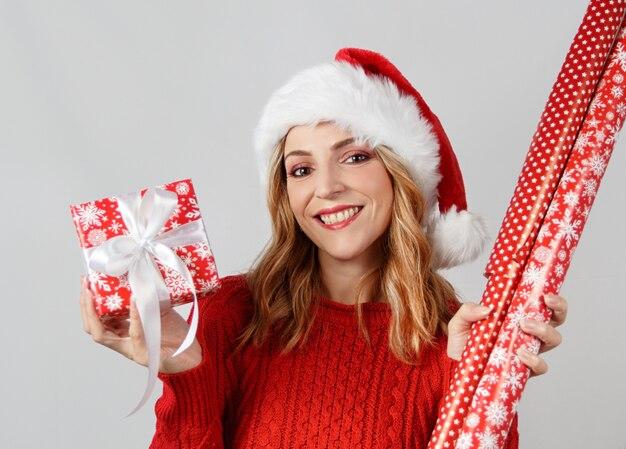 Jonge vrouw in kerstmuts bedrijf verpakt aanwezig