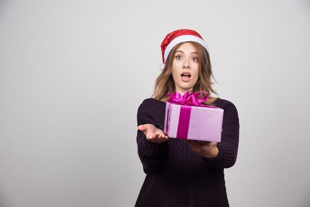 Jonge vrouw in kerstmuts die een geschenkdoos aanbiedt.