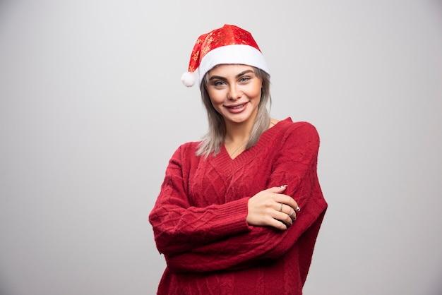 Jonge vrouw in kerstmuts die zich voordeed op een grijze achtergrond.