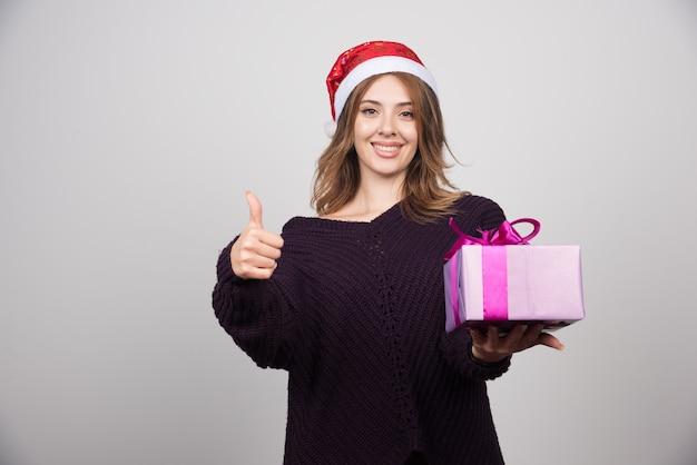 Jonge vrouw in kerstmuts met geschenkdoos met een duim omhoog.