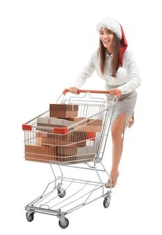 Jonge vrouw in kerstmuts met geschenken in winkelwagen. tweede kerstdag concept