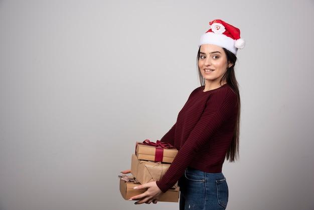 Jonge vrouw in kerstmuts met kerstcadeautjes op een grijze achtergrond.