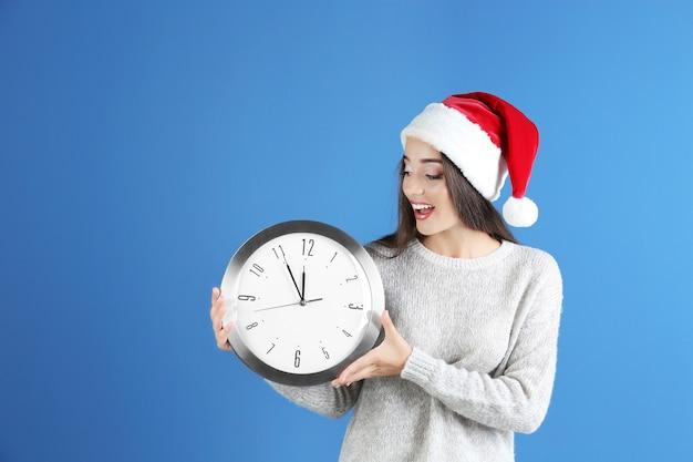 Jonge vrouw in kerstmuts met klok op kleur oppervlak. kerst aftellen concept