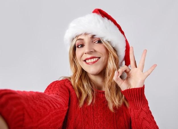 Jonge vrouw in kerstmuts selfie maken en ok teken doen