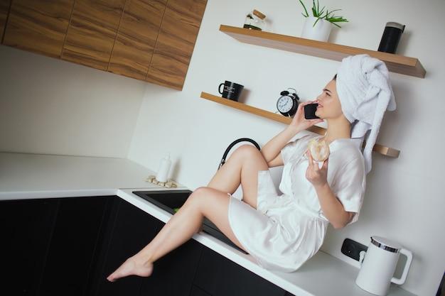 Jonge vrouw in keuken tijdens quarantaine. aantrekkelijk meisje zitten en praten over de telefoon na het douchen houd donut in de hand. sexy meisje brengt tijd door in de keuken.