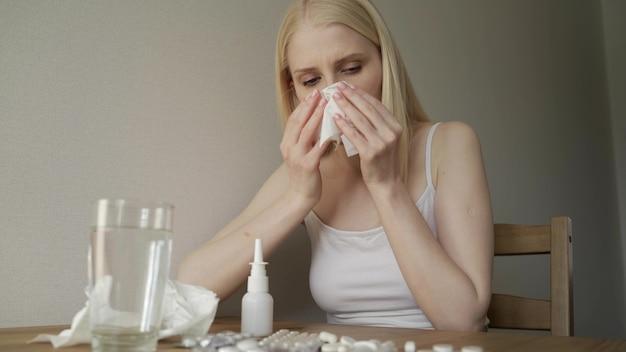Jonge vrouw in keuken tijdens quarantaine. meisje aan tafel zitten en niezen.