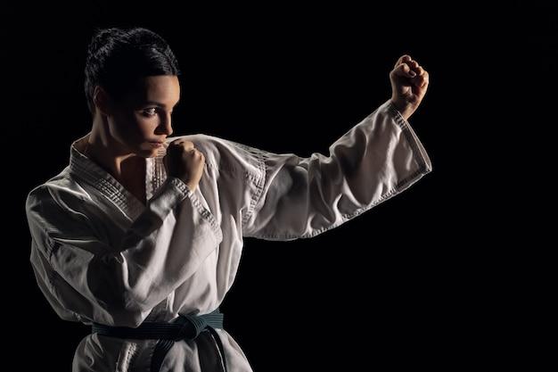 Jonge vrouw in kimono in gevechtshouding op een zwarte achtergrond