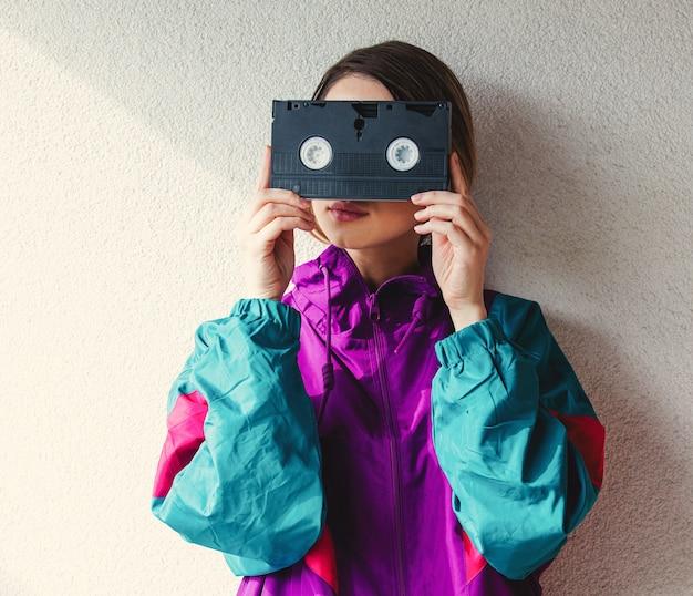Jonge vrouw in kleren van de jaren '90stijl die vhs-cassette houden
