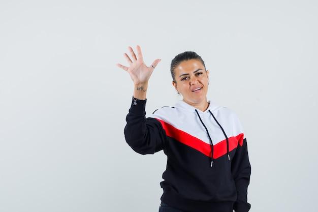 Jonge vrouw in kleurrijke sweater zwaaiende hand voor groet en op zoek tevreden, vooraanzicht.