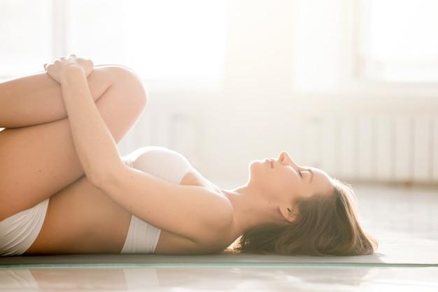 Jonge vrouw in knieën tot kist vormen, witte achtergrond, close-up