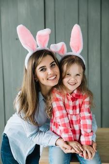 Jonge vrouw in konijntjesoren die dochter koesteren