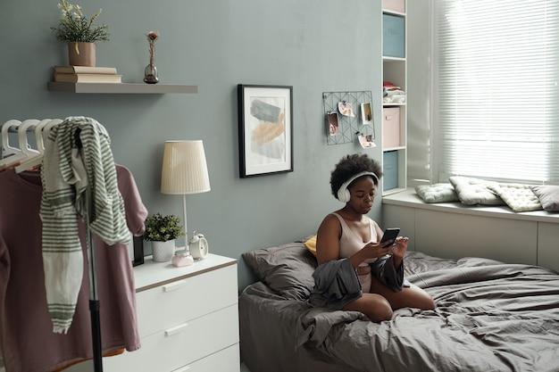 Jonge vrouw in koptelefoon scrollen door afspeellijst