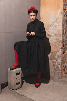 Jonge vrouw in kunstactie die de grootste schilderijen en zijn kunstenaars opnieuw maakt op een ouderwetse muur.