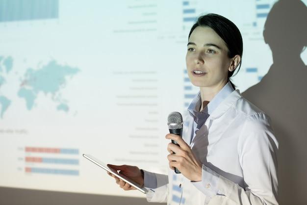 Jonge vrouw in laboratoriumjas met behulp van proefschrift plan op tablet tijdens de presentatie van project op medische conventie
