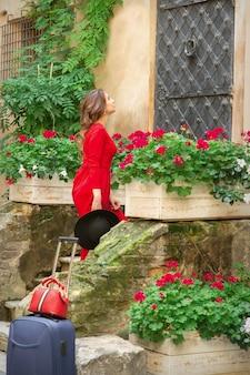 Jonge vrouw in lange rode jurk traplopen naar oude deur buiten in de oude stad