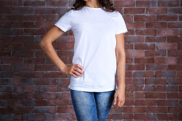 Jonge vrouw, in, leeg wit, t-shirt, staand, tegen, bakstenen muur, close-up