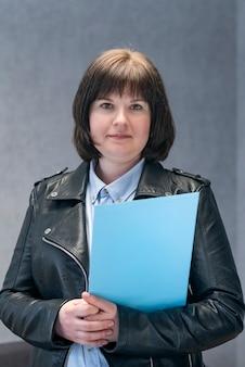 Jonge vrouw in leren jas houdt documenten vast. zakenvrouw in bikerjacks. moderne zakenvrouw.