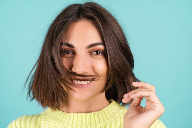 Jonge vrouw in lichtgroene trui glimlachend